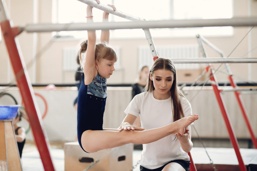 Child gymnastics balance beam.  Girl gymnast athlete during an exercise horizontal bar in gymnastics competitions. Coach with child.