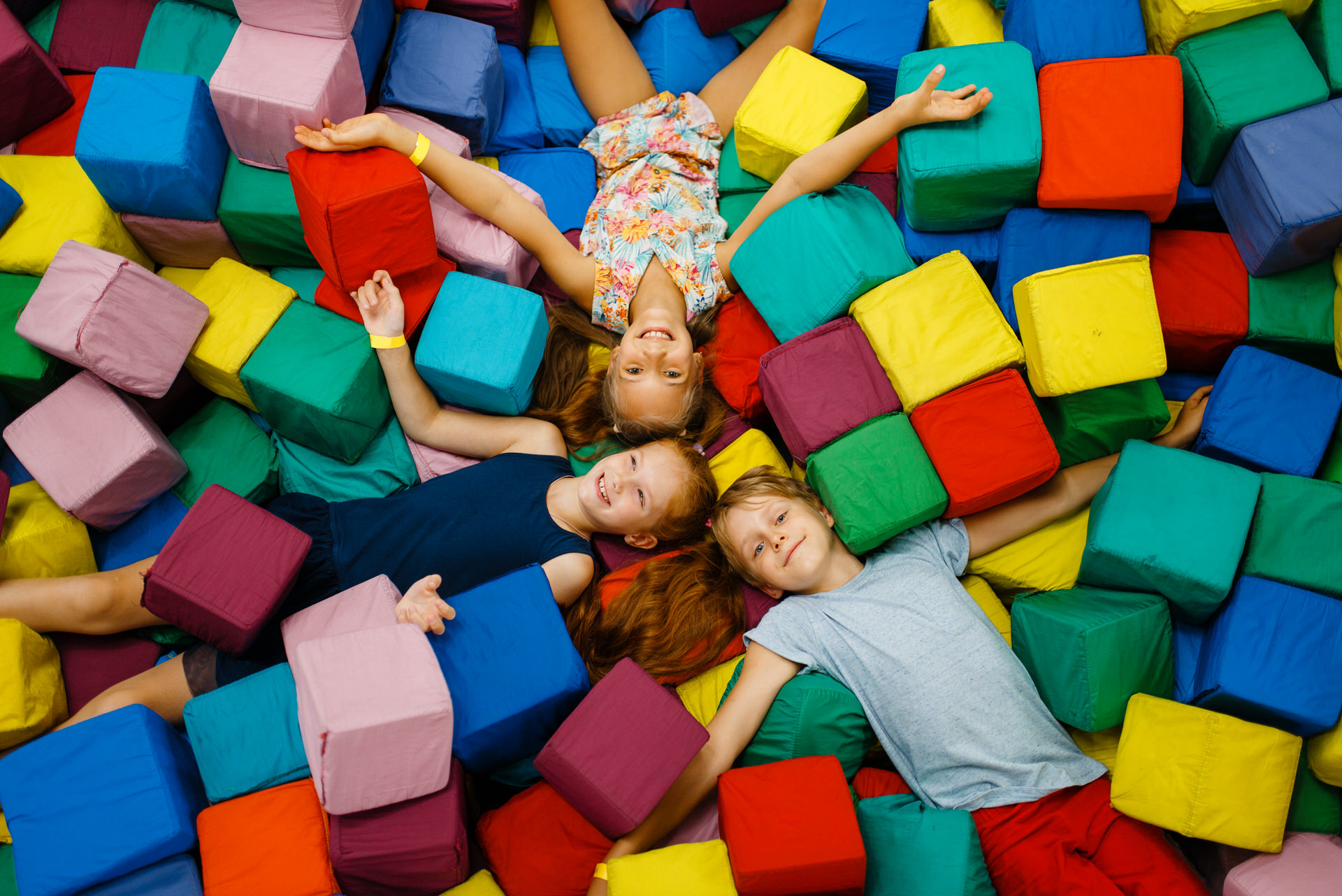 Happy children lying in soft cubes, playground in entertainment center. Play area indoors, play room