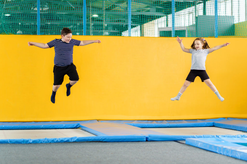 Happy smiling small kids jumping on indoors trampoline during leisure sport training